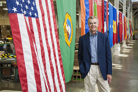 Rod Schneidmiller, founder and president of RESCUE! Pest Control Products, stands with the American flag, the Washington state flag, and other flags representative of our employees' nationalities.